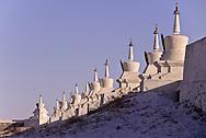 Mongolia. Erden Zuu monastery. Karakorum  /  EnHiver monastère de Erden Zuu/  Muraille de stupas entourant le monastère de ERDENI ZUU (XVI me siècle)./  Érigé en 1743, ce mur d'enceinte n'était à l'origine qu'une sorte de remblai en terre argileuse et graviers, d'une épaisseur de 2,50 mètres environ. Reconstruit en 1804 en briques peintes en blanc avec 56 stupas ou suburgan encastrés à espace régulier, ce rempart avait une fonction défensive. Avec le temps, les stupas ont augmenté pour atteindre le nombre actuel de 108 : 25 de chaque côté et 2 à chaque angle. (QARAQORIN,
