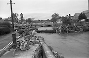 """Flooding at the Dodder..1986..26.08.1986..08.26.1986..28th August 1986..As a result of Hurricane Charly (Charlie) heavy overnight rainfall was the cause of severe flooding in the Donnybrook/Ballsbridge areas of Dublin. In a period of just 12 hours it was stated that 8 inches of rain had fallen. The Dodder,long regarded as a """"Flashy"""" river, burst its banks and caused great hardship to families in the 300 or so homes which were flooded. Council workers and the Fire Brigades did their best to try and alleviate some of the problems by removing debris and pumping out some of the homes affected..Note: """"Flashy"""" is a term given to a river which is prone to flooding as a result of heavy or sustained rainfall...Picture shows work men at the site where the road had subsided near the bridge over the Dodder at Ballsbridge, Dublin.The picture also shows damage to a water main and the amount of debris carried down river by the flood."""