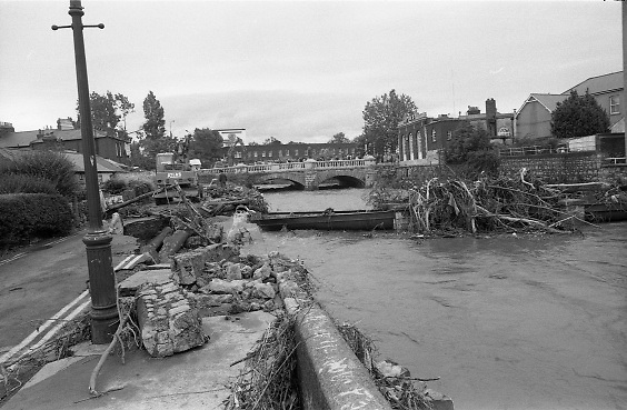 "Flooding at the Dodder..1986..26.08.1986..08.26.1986..28th August 1986..As a result of Hurricane Charly (Charlie) heavy overnight rainfall was the cause of severe flooding in the Donnybrook/Ballsbridge areas of Dublin. In a period of just 12 hours it was stated that 8 inches of rain had fallen. The Dodder,long regarded as a ""Flashy"" river, burst its banks and caused great hardship to families in the 300 or so homes which were flooded. Council workers and the Fire Brigades did their best to try and alleviate some of the problems by removing debris and pumping out some of the homes affected..Note: ""Flashy"" is a term given to a river which is prone to flooding as a result of heavy or sustained rainfall...Picture shows work men at the site where the road had subsided near the bridge over the Dodder at Ballsbridge, Dublin.The picture also shows damage to a water main and the amount of debris carried down river by the flood."