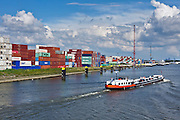 Rotterdam harbor with stacked containers and water-to-water transshipment vessel