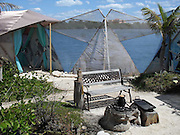 """Eco-pioneer Richard """"Rishi"""" Sowa designed and built an artificial island kept afloat by 100,000 plastic bottles.<br /> <br /> Spiral Island II is actually Rishi Sowa's second artificial island. He built the first one in 1998, near Puerto Aventuras, using 250,000 plastic bottles to keep it afloat. Sadly, his recycled island was destroyed in 2005, when Hurricane Emily passed through the area. Most of Spiral Island was washed up on the beach, but Sowa decided to build a whole new island, in a safer area.<br /> <br /> And that's how Spiral Island II came to be. With the help of volunteers, Rishi Sowa gathered around 100,000 plastic bottles and hand-built his second recycled island, in a lagoon that offers protection from bad weather. The new island features a house, beaches, 2 ponds and a solar-powered waterfall, but its creator says Spiral Island II is and always will be an eco-work-in-progress. Although smaller than its predecessor (only 20 meters in diameter), you can expect the new Spiral Island to increase in size, significantly.<br /> <br /> One of the most impressive DIY projects ever attempted, Spiral Island has inspired volunteers to come to Mexico and help Rishi Sowa improve his creation. But while some believe it a perfect environmental design, built entirely of recycled materials, there is some controversy surrounding Spiral Island. There are those who believe that if the island gets destroyed by a hurricane, again, the materials used to build it (mainly plastic bottles, sand, mangrove plants) will litter the waters of the Atlantic. <br /> Photo Shows: main communal area and wind breaker curtain<br /> ©Spiral Island /Exclusivepix"""