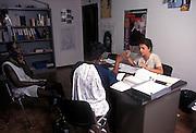 Elena Bartoli in charge of the Assistance Center for Immigrants, speaks with Ghananian immigrants at his office in Nonantola, June, 1996...2006 Nonantola (Modena), centro assistenza immigrati del Comune;La responsabile Elena Bartoli con due immigrati ghanesi.