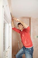 Man preparing wall of unrenovated room