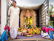 "29 SEPTEMBER 2012 - NAKORN NAYOK, THAILAND:   A man stands in front of his statue of Ganesh that he brought to the temple to be blessed during observances of Ganesh Ustav at Wat Utthayan Ganesh, a temple dedicated to Ganesh in Nakorn Nayok, about three hours from Bangkok. Ganesha Chaturthi also known as Vinayaka Chaturthi, is the Hindu festival celebrated on the day of the re-birth of Lord Ganesha, the son of Shiva and Parvati. The festival, also known as Ganeshotsav (""festival of Ganesha"") is observed in the Hindu calendar month of Bhaadrapada, starting on the the fourth day of the waxing moon. The festival lasts for 10 days, ending on the fourteenth day of the waxing moon. Outside India, it is celebrated widely in Nepal and by Hindus in the United States, Canada, Mauritius, Singapore, Thailand, Cambodia, Burma , Fiji and Trinidad & Tobago.    PHOTO BY JACK KURTZ"
