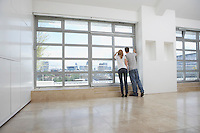 Couple looking out of window in empty apartment