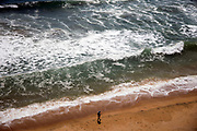 VARKALA, INDIA - 1st October 2019 - Aeiral birds eye view of fisherman walking along sandy beach with crashing ocean waves in background, Varkala Cliff Beach, Kerala, Southern India