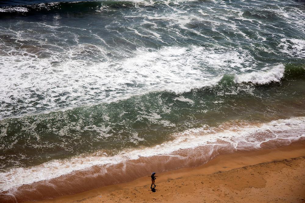 VARKALA, INDIA - 1st October 2019 - Aeiral birds eye view of fisherman walking along sandy beach with crashing ocean waves in background, Varkala Cliff Beach, Kerala, Southern India