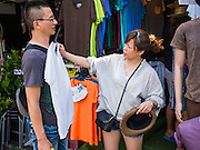 18 APRIL 2015 - BANGKOK, THAILAND:  Tourists from China look at clothes in the Chatuchak Weekend Market in Bangkok. Chatuchak Weekend Market in Bangkok is reportedly the largest market in Thailand and the world's largest weekend market. Frequently called J.J., it covers more than 35 acres and contains upwards of 5,000 stalls.       PHOTO BY JACK KURTZ