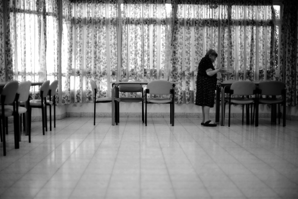 A Holocaust survivor arranges the tables in the dining room of the Shaar Menashe mental health center for holocaust survivors in Pardes Hanna, Israel on Jan 3, 2011.