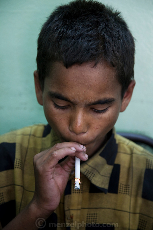 A young porter Alamin Hasan, smokes a cigarette at the Kamlapur train station in Dhaka, where he earns a living by offering to carry passengers' bags.  (From the book What I Eat: Around the World in 80 Diets.) MODEL RELEASED.