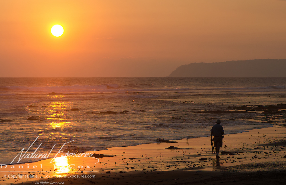 A man walking along a beach during sunset in Costa Rica.