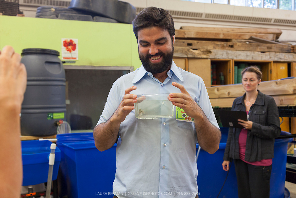 FoodShare's Justin Nadeau  holds a small tilapia while explaining aqualculture to workshop particpants at  the Field to Table Schools Program's Educators' Workshop at Bendale school.
