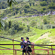 Black Hmong women crossing a bridge in mountains of Northern Vietnam