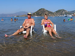 Couple on holiday sitting on chairs in the sea dabbling their toes; Marmaris; Turkey