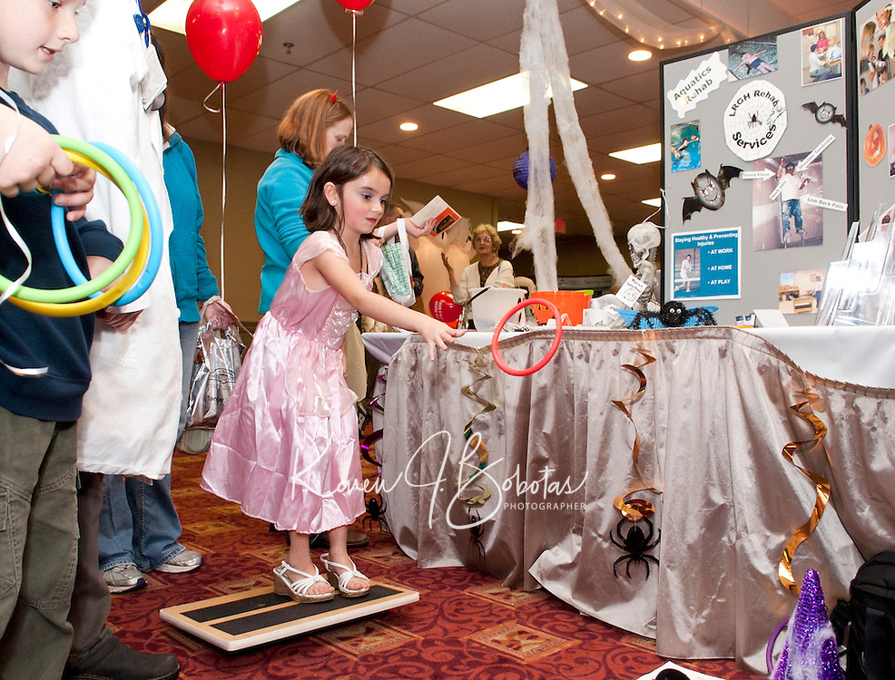 Avery Smock enjoys a game of ring toss at the LRGH Rehab Services booth during the 2011 Business BooFest presented by PSNH Thursday evening at the Opechee Inn and Spa Conference Center.  (Karen Bobotas/for the Laconia Daily Sun)