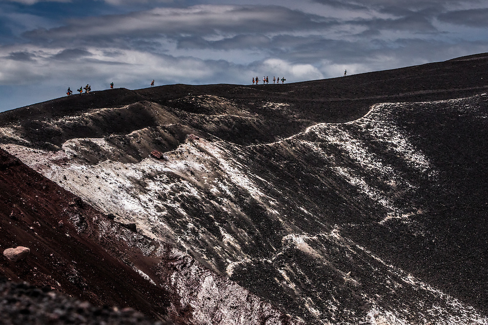 LEON, NICARAGUA - SEPTEMBER 18, 2014: A group of tourists hike across the ridge of one of the craters of Cerro Negro volcano. Guided tours are available from $29 USD to board down the volcano, located an hour outside of Leon. PHOTO: Meridith Kohut