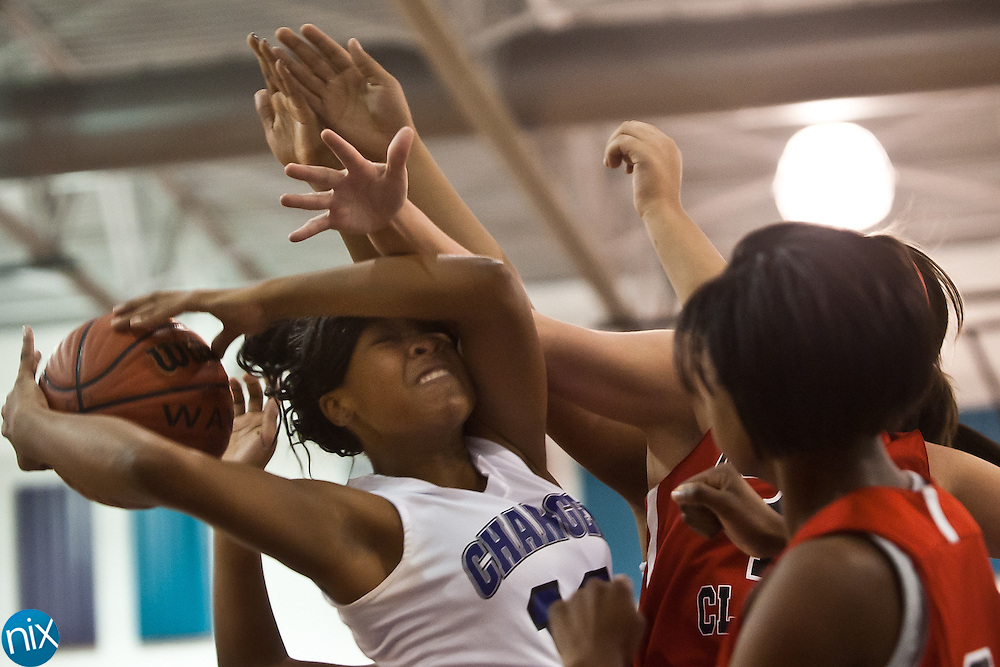 Cox Mill's Ivy Arrington fights for a rebound against Covenant Classical during the first round of the CMC-Northeast Holiday Basketball Tournament at Cox Mill High School Tuesday. (Photo by James Nix)