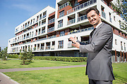 Portrait of smiling real estate agent presenting office building