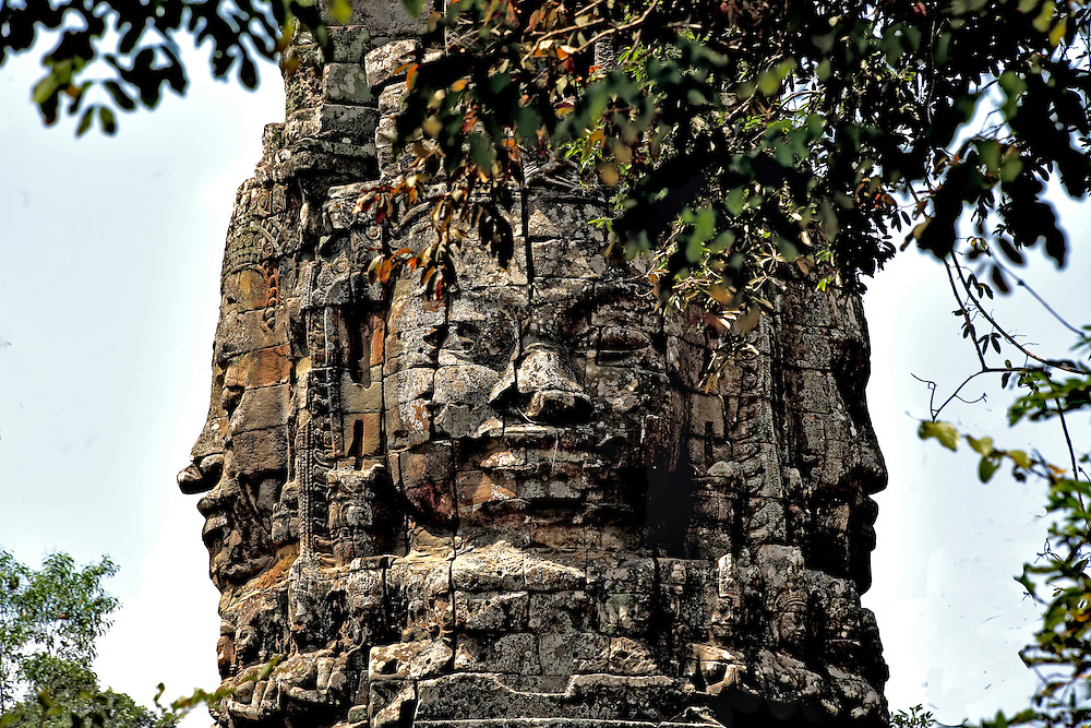 Top of a gopura, or gate, to a temple precinct, with sculptured heads of the king or a god facing in each of the four cardinal directions as a symbol of protection for the people.