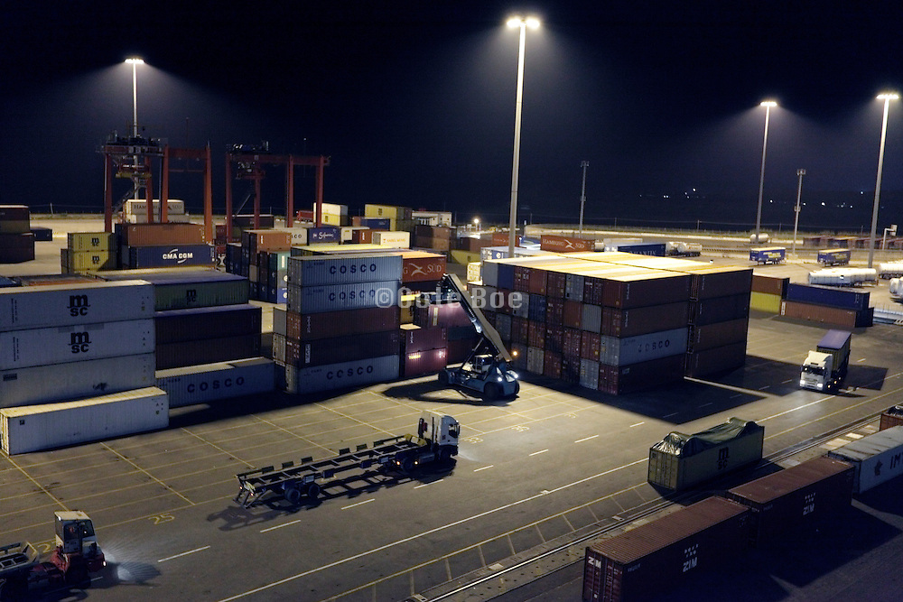 stacking containers in harbor during night