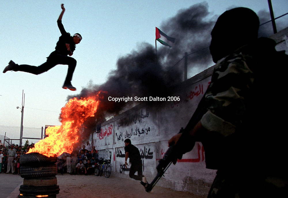 A teenage boy jumps over burning tires at a training camp for the Al-Aqsa Martyrs Brigade in Gaza City. The group, which emerged shortly after the outbreak of the current Palestinian intifada, has carried out operations against Israeli soldiers and settlers in the West Bank and Gaza, and suicide attacks on civilians inside Israel. In March 2002, after a deadly al-Aqsa suicide bombing in Jerusalem, the U.S. State Department added the group to the U.S. list of foreign terrorist organizations. (Photo/Scott Dalton)