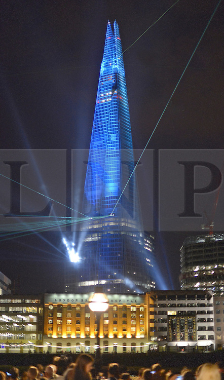 © Licensed to London News Pictures. 05/07/2012. London, UK The light show seen from Old Billingsgate Market on the banks of the River Thames. The tallest building in Europe, The Shard,  is inaugurated today, 5th July 2012, with a light show visible across London.  Laser Beams were fired from its summit to 15 London skyscrapers and landmarks such as the Gherkin and Canary Wharf. The laser show culminated in the illumination of the Shard itself. . Photo credit : Stephen Simpson/LNP