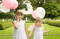 Two young girls in garden holding balloons smiling portrait