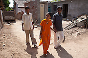 Hansa who is deaf and blind walks through her village accompanied by her father and brother.  Hansa is supported by Sense International and the Dhanki Community Project to lead a more independent life.