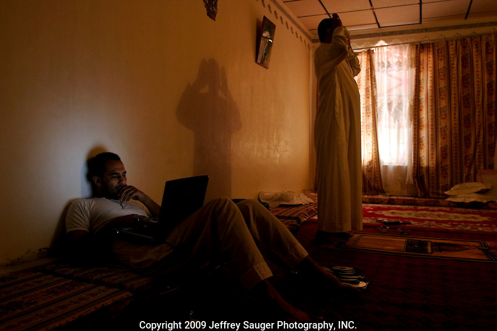 Emad Al-Kasid, left, works on his laptop, as his father Malik Al-Kasid, right, performs Dhuhr (noon prayer) one of five prayers Muslims are commanded to perform each day at their rented house in Nasiriyah, Iraq. ..The Al-Kasid family fled Iraq after the Gulf War and their part in the uprising against Saddam Hussein in 1991, spent 3 years in Rafha, Saudi Arabia and finally settled in Dearborn, MI. The family hasn't been home to Iraq in 13 years.
