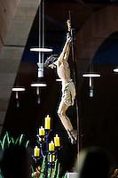 """È stata inaugurata il 1° luglio 2004, la nuova Chiesa di San Pio da Pietrelcina progettata dall'architetto Renzo Piano. Esattamente 45 anni prima, nel 1959,  veniva inaugurata la chiesa """"grande"""" di Santa Maria delle Grazie. .Sorta a fianco del santuario e convento in cui visse il frate, ha la forma di una conchiglia e la sua pianta ricorda quella della spriale archimedea. Enormi archi parto dal perimetro esterno e terminano nel fulcro della """"conchiglia"""" dove è posto l'altare. Possenti staffe d'acciaio, ancorate agli archi, sorreggono la volta che ricoperta di rame preossidato espone alla vista un intenso un colore verde-rame.   .Con i suoi 6000 mq, è la seconda chiesa più grande in Italia per dimensioni, dopo il Duomo di Milano. Può ospitare oltre 7000 persone e per la sua realizzazione sono state impiegati 30.000 metri cubi di calcestruzzo, 1.320 blocchi in pietra di Apricena, 70.000 metri cubi di scavo in roccia, 60.000 chili di acciaio, 500 mq di vetro, 19.500 mq di rame preossidato. Ogni anno è meta di oltre sei milioni di pellegrini..Nella foto il crocifisso sospeso, al centro della chiesa."""