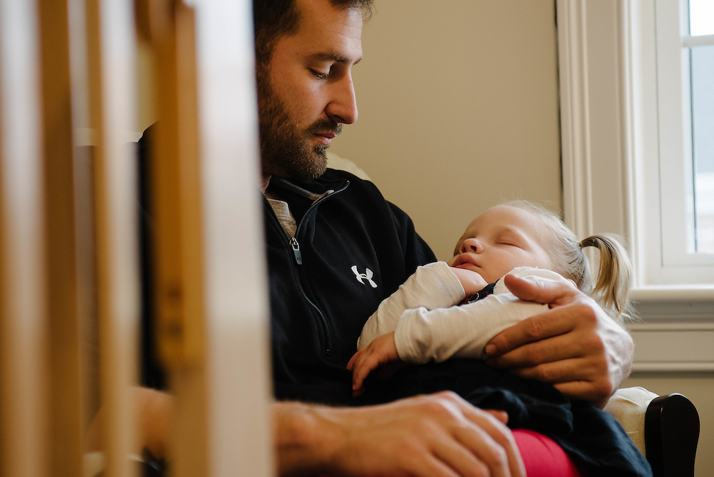 A father about to put his daughter in her crib for an afternoon nap in their new home in Wrentham, MA, photographed for the Mass Housing Annual Report.