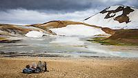 Hiker taking a break, reading a book. Hveradalir Geothermal Valley in Kerlingarfjöll Mountain Range, Interior of Iceland.
