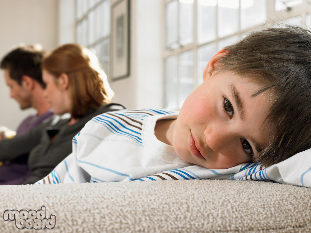 Boy (3-6) with parents on couch (portrait)