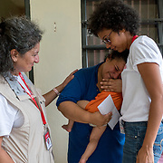 NOVEMBER 17, 2017&ndash;MARICAO, PUERTO RICO&mdash;<br /> Mercy Corps staffers Karla Pe&ntilde;a, right, and Pardis Barjesteh, comfort a crying Stephanie Colon Medina, 27, after she received cash and a water filtration system from them. Colon Medina is holding her 1 year old son Anthony Jaffeth.<br /> (Photo by Angel Valentin)
