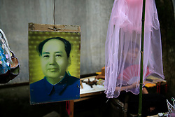 A souvenir hawker fans herself behind a veil at her stall selling Mao Zedong souvenirs outside the 'Water Dripping Cave' compound, where Mao Zedong stayed briefly for 11 days in 1966 and is thought to have contemplated the start of the Cultural Revolution there in Shaoshan, Hunan Province in central China, 28 April 2016. Shaoshan is the hometown of former Communist leader Mao Zedong, popularly known as Chairman Mao. Thousands of visitors descend on this small Chinese town burrowed in the hills of Central China's Hunan province to pay homage to the great helmsman everyday. It is one of the core sites of the 'Red Tourism' industry, where communist party cadres and ordinary Chinese tourists alike seek to relive the experiences and rekindle the spirit of the revolutionaries.