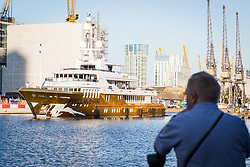 © Licensed to London News Pictures. 17/09/2019. London, UK. A man watches as gold wrapped, 175 feet long superyacht, Bellami.com arrives in East India Dock. It took 13 days and 600sqm of gold chrome vinyl wrap to cover the superyacht formally known as 'Kinta' at the Port of Viareggio in Italy this year and is the largest chrome yacht wrap done fully in the water and possibly the largest chrome wrap ever. As Bellami.com arrived, it was noticed that some of the chrome wrap was already damaged and missing. Photo credit: Vickie Flores/LNP
