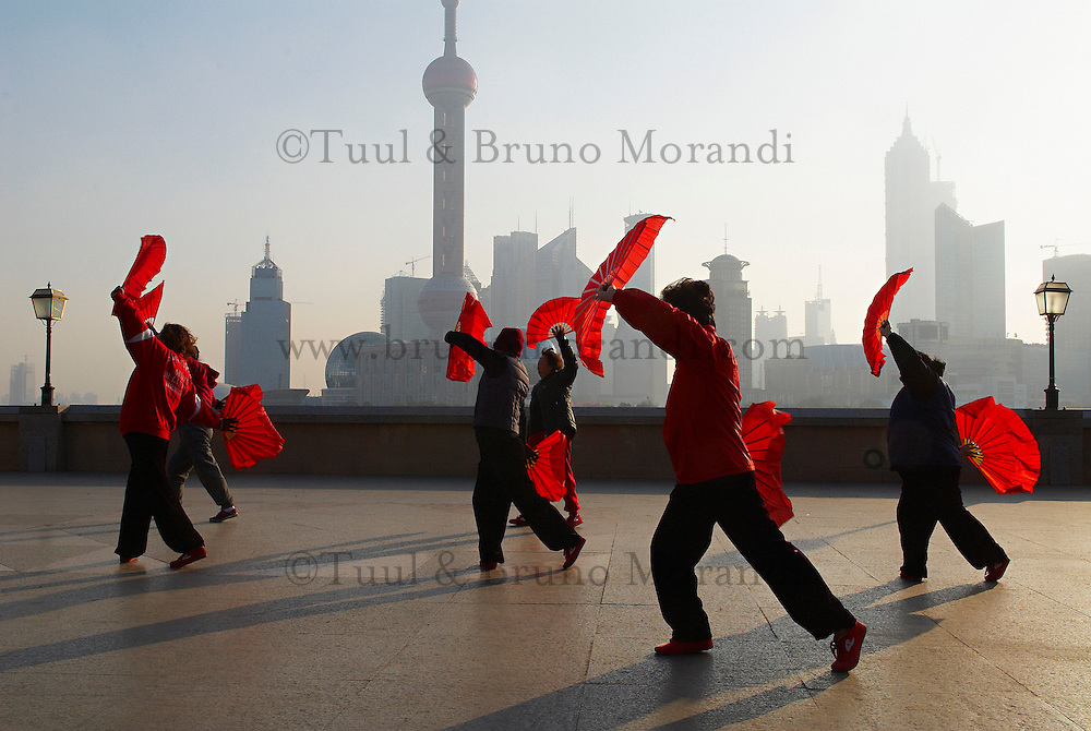 Chine. Shanghai. Excercices matinal sur le Bund. // China. Shanghai. Chinese women dance with red fans on the bund in Shanghai for exercise every morning.