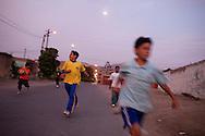 Children run down the street on Tuesday, Apr. 7, 2009 in Ventanilla, Peru.