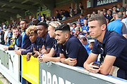 AFC Wimbledon goalkeeper Nicola Tzanev (25), AFC Wimbledon defender Paul Kalambayi (30), AFC Wimbledon midfielder Neset Bellikli (27), AFC Wimbledon defender Tom Scott (23), AFC Wimbledon defender Terell Thomas (6) watching the game during the EFL Sky Bet League 1 match between AFC Wimbledon and Coventry City at the Cherry Red Records Stadium, Kingston, England on 11 August 2018.