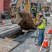 Saveway Construction Enterprises backhoe operator lifting steel covering plate so crew can  dig up street for replacement of new gas pipes in Waverly Place,  Greenwich Village, NYC. <br />