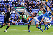 Kwesi Appiah of AFC Wimbledon looks to score as Christy Pym of Peterborough United comes out to chest the ball away during the EFL Sky Bet League 1 match between Peterborough United and AFC Wimbledon at London Road, Peterborough, England on 28 September 2019.