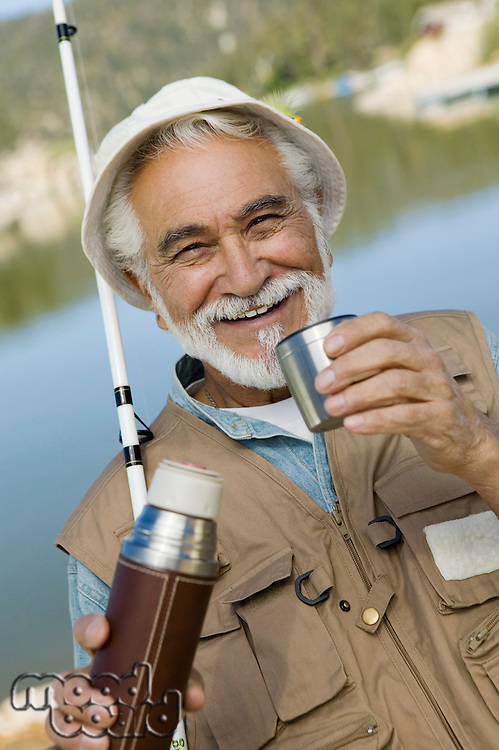 Man Fishing and Drinking Coffee