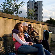 Nederland Rotterdam 22 augustus 2008 20080822 Foto: David Rozing .Allochtone jongen zit / chilt in het avondzonnetje op bankje in Kralinger Esch met zijn armen om de 2 meiden aan zijn beide zijden. Op zijn tshirt staat een afbeelding van zijn voorkeur voor vrouwen. Op het tshirt staat een afbeelding van een bedekte moslima vrouw in een boerka en een afbeelding van een half ontblote vrouw in bikini. Tekst tshirt: Moslima, your girlfriend Afbeelding vrouw kikini, my girlfriend.Young allochthonous boy chilling with two young girls at his side on bench. The boy wears tshirt with his prefenrence for women, images on the tshirt: a fully covered islamitic woman (your girlfriend) and a half naked western woman ( my girlfriend). His preference is the half naked woman. Sexual, mixed, sexualising, sexualised, modern,reject, condemn, islamitic culture, women, girl, girls, moral, morals, sliding morality,  interracial, youth, funny, clothes, clothing, sexsymbol, symbol, generation, multicultural, clashing of cultures, culture, indoctrinating, indoctrinated, different, against, dissolute, wanton, prudish, prudery, streetculture, ..Foto David Rozing