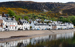 View of whitewashed houses along shore in Ullapool on the North Coast 500 scenic driving route in northern Scotland, UK