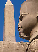 EGYPT, ANCIENT MONUMENTS, KARNAK Temple of Amun; statue of King Tut with obelisk beyond