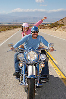 Bikers riding on desert road