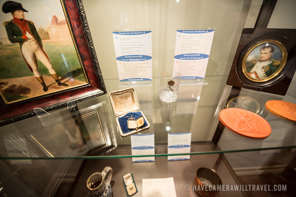 The room used by Napoleon, filled with souvenirs and personal affects that belonged to the Emporer. A display case includes a number of small items related to Napoleon including, at center of frame, a locket with some stands of Napoleon's hair. Next to the field where the Battle of Waterloo took place in 1815, the Ferne du Caillou is famous as the place where Napoleon spent the night before the battle. It is now a museum.