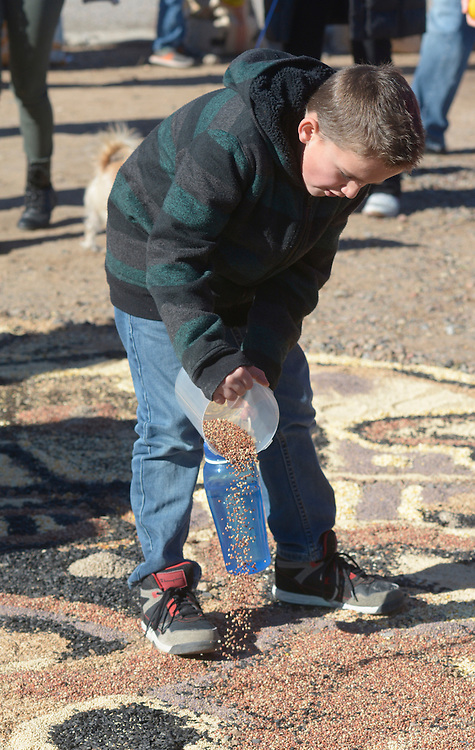 gbs121816l/ASEC -- Orion Amburgey, 8, of Albuquerque, pours seeds on the Winter Solstice Seed Mandala at the Open Space Visitor Center on Sunday, December 18, 2016. The community art project is a way to feed the birds at the center.(Greg Sorber/Albuquerque Journal)
