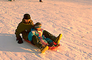 Cousins sledding down hill ages 22 and 4.  St Paul  Minnesota USA