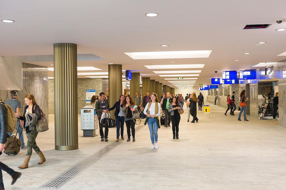 Nederland, Breda, 20140912.<br /> Reizigers in de nieuwe voetgangerspassage. De noordkant van het station in gebruik is genomen. Het compleet nieuwe station van Breda brengt reizen, wonen, werken en winkelen op een moderne en comfortabele manier samen. Door een nieuw busperron voor twintig bussen, parkeerruimte voor 4.400 fietsen en meer dan 700 auto&rsquo;s, woningen, kantoren en winkels in het station zelf. Opgezet op een ruime en toegankelijke manier, met een brede voetgangerspassage, overzichtelijke pleinen en brede wegen. De zes sporen en drie perrons op station Breda bieden ruimte aan 16 treinen per uur.<br /> <br /> Netherlands, Breda, 20140912.<br /> The completely new railway station of Breda will travel, live, work and shop in a modern and comfortable way together. A new bus platform for twenty buses, parking for 4,400 bikes and over 700 cars, homes, offices and shops in the station itself. Mounted on a spacious and accessible way, with a wide pedestrian passage, clear squares and wide roads. The six tracks and three platforms at Breda station for up to 16 trains per hour.
